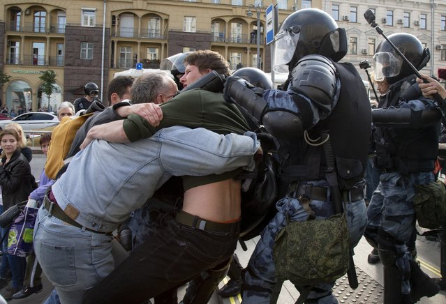 Police officers try to detain protestors during an unsanctioned rally in the center of Moscow, Russia, Saturday, August 3, 2019. Moscow police detained more than 300 people Saturday who are protesting the exclusion of some independent and opposition candidates from the city council ballot, a monitoring group said. (Photo by Alexander Zemlianichenko/AP Photo)