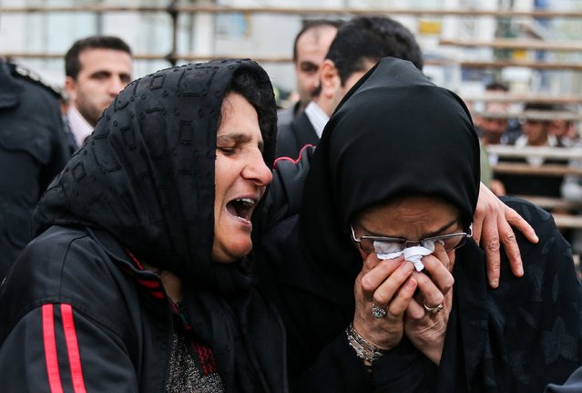 The mother of an Iranian man Balal (L), who killed an Iranian youth Abdolah Hosseinzadeh in a street fight with a knife in 2007, cries with the mother of Abdolah Hosseinzadeh after she forgave Balal, giving him an emotional slap prior to removing the noose around his neck in the gallows during his execution ceremony in the northern city of Nowshahr on April 15, 2014. The mother of  Abdolah Hosseinzadeh spared the life of Balal, her son's convicted murderer, with an emotional slap in the face as he awaited execution prior to removing the noose around his neck. (Photo by Araash Khamooshi/AFP Photo/ISNA)