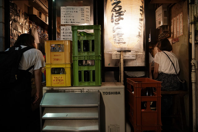 A woman, left, peeks into a packed izakaya-style restaurant at the Golden Gai in the Shinjuku district of Tokyo, July 28, 2019. (Photo by Jae C. Hong/AP Photo)