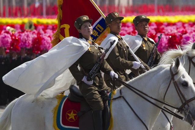 North Korean soldiers ride by on horses in front of flower waving civilians during a mass military parade in Pyongyang's Kim Il Sung Square to celebrate 100 years since the birth of the late North Korean founder Kim Il Sung on Sunday, April 15, 2012. (Photo by David Guttenfelder/AP Photo)