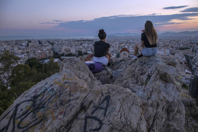 In this Thursday, July 4, 2019 photo, two young women sit on a rock covered with graffiti as they admire the view of Athens during a sunset. (Photo by Petros Giannakouris/AP Photo)