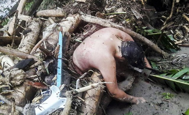 Handout picture released by the Colombian Army press office showing the corpse of a man caught in a mudslide caused by heavy rains, in Mocoa, Putumayo department, on April 1, 2017. Mudslides in southern Colombia -caused by the rise of the Mocoa River and three tributaries- have claimed at least 16 lives and injured some 65 people following recent torrential rains, the authorities said. (Photo by AFP Photo/Ejercito De Colombia)