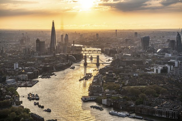 Sunset over London. Looking up the River Thames past Wapping to Tover Bridge, the Shard and the City of London. (Photo by Jason Hawkes/Caters News Agency)