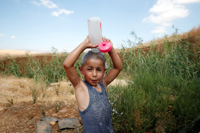 A Palestinian boy pours water onto himself to cool off in Jordan Valley in the Israeli-occupied West Bank on August 21, 2019. (Photo by Mohamad Torokman/Reuters)
