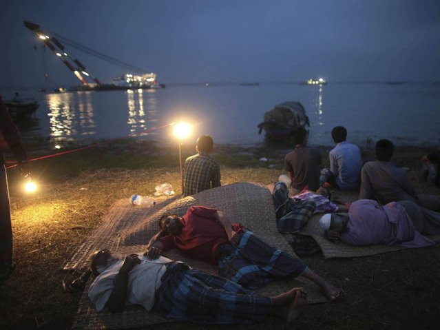 Relatives sleep while they wait for news of passengers after the M.V. Miraj-4 ferry capsized, by the Meghna river at Rasulpur in Munshiganj district. (Photo by Andrew Biraj/Reuters)