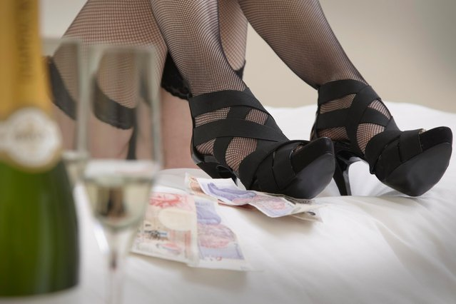 Cash next to woman on bed in stockings & heels. (Photo by Getty Images)