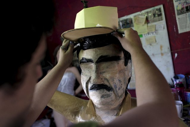 "A worker attaches a hat to a pinata depicting the drug lord Joaquin ""El Chapo"" Guzman at a workshop in Reynosa, July 21, 2015. (Photo by Daniel Becerril/Reuters)"