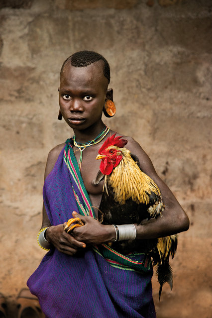 A girl from the Kara tribe holds a rooster, Dus Village, Omo Valley, Ethiopia. (Photo by Steve McCurry/The Guardian)