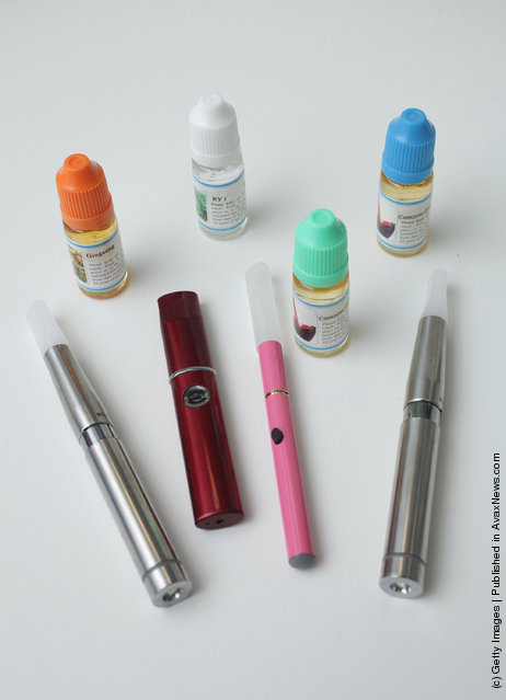 Electronic cigarettes lie in front of bottles containing the flavoured liquids they use at a shop