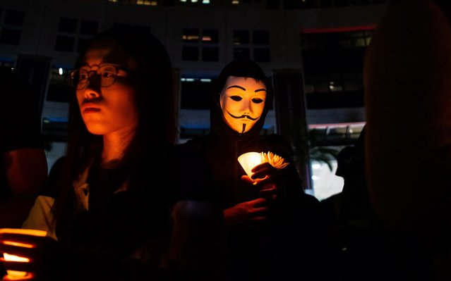 """Masked students light candles during a ceremony to pay tribute to Chow Tsz-lok, 22, a university student who fell during protests at the weekend and died early on Friday morning, at the Hong Kong University of Science and Technology (HKUST) on November 08, 2019 in Hong Kong, China. Hong Kong slipped into a technical recession on Thursday after anti-government demonstrations stretched into its fifth month while protesters continue to call for Hong Kong's Chief Executive Carrie Lam to meet their remaining demands since the controversial extradition bill was withdrawn, which includes an independent inquiry into police brutality, the retraction of the word """"riot"""" to describe the rallies, and genuine universal suffrage. (Photo by Billy H.C. Kwok/Getty Images)"""