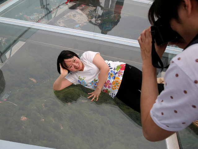 A woman lies to pose for her souvenir picture on the glass sightseeing platform on Shilin Gorge in Beijing, China, May 27, 2016. (Photo by Kim Kyung-Hoon/Reuters)