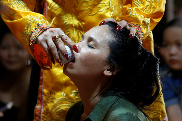 Pham Thi Thanh drinks a glass of water used as a treatment during a medium ritual at a Hau Dong ceremony at Phu Day temple in Nam Dinh province, Vietnam, May 7, 2017. (Photo by Reuters/Kham)
