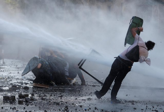A water cannon hits a demonstrator during a protest against Chile's government in Santiago, Chile on November 20, 2019. (Photo by Goran Tomasevic/Reuters)