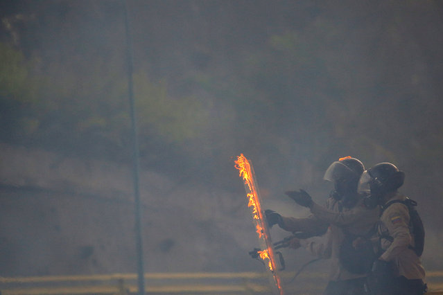 A member of the Venezuelan National Guard reacts after a molotov cocktail impacted nearby during riots at a protest against Venezuela's President Nicolas Maduro in Caracas, Venezuela, May 27, 2017. (Photo by Carlos Barria/Reuters)