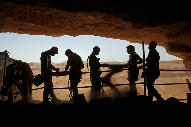 Volunteers with the Israeli Antique Authority work at the Cave of the Skulls, an excavation site in the Judean Desert near the Dead Sea, Israel June 1, 2016. (Photo by Ronen Zvulun/Reuters)
