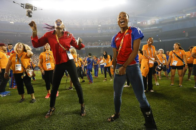 Athletes Priscilla Frederick, left, and Marlena Hilari Wesh, of Antigua and Barbuda, dance during a performance at the closing ceremony of the Pan Am Games Sunday, July 26, 2015, in Toronto. (Photo by Julio Cortez/AP Photo)