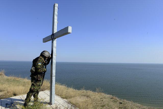 A serviceman of the pro-Ukrainian Saint-Maria battalion prays near the cross, installed on a seashore near the eastern Ukrainian city of Mariupol, on October 2, 2014. (Photo by Alexander Khudoteply/AFP Photo)