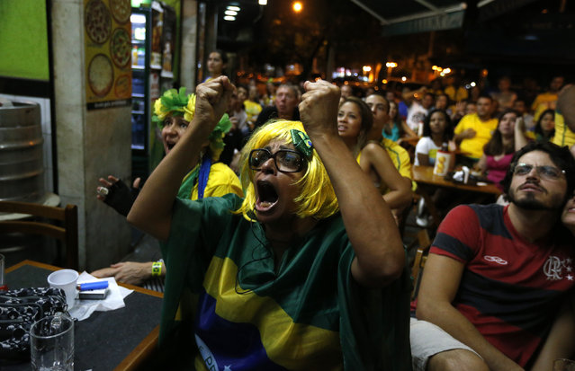 Brazilian soccer fans celebrate Brazil's goal against Croatia during the opening match of the 2014 World Cup, at a bar in Rio de Janeiro June 12, 2014. (Photo by Pilar Olivares/Reuters)