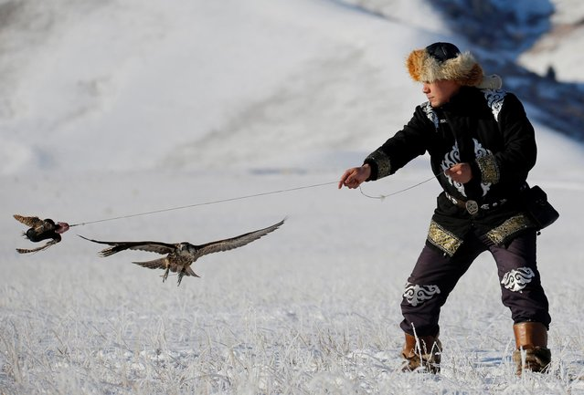 A hunter performs with his tamed hawk during a traditional hunting contest outside the village of Kaynar in Almaty region, Kazakhstan on December 8, 2019. (Photo by Pavel Mikheyev/Reuters)