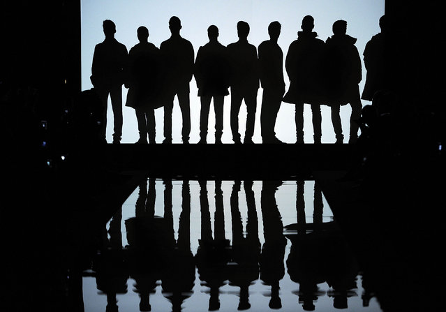 Models are silhouetted during the presentation of Ermanno Scervino men's Spring-Summer 2015 collection, part of the Milan Fashion Week, unveiled in Milan, Italy, Tuesday, June 24, 2014. (Photo by Giuseppe Aresu/AP Photo)
