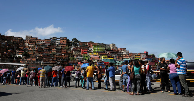 People stand in line as they wait to buy staple items and basic food at the parking lot of a supermarket in Caracas, Venezuela June 10, 2016. (Photo by Carlos Garcia Rawlins/Reuters)