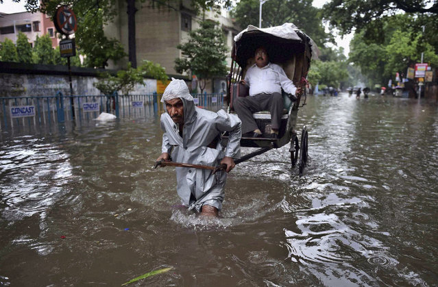 An Indian hand rickshaw puller transports a man to his destination through a water logged street after heavy rains in Kolkata, India, Saturday, August 1, 2015. Cyclonic storm Komen weakened into a depression after making landfall over Bangladesh coast on Thursday, causing heavy rainfall in several parts of the eastern Indian state of West Bengal and throwing normal life out of gear as most parts of the city were submerged, according to local reports. (Photo by Swapan Mahapatra/Press Trust of India via AP Photo)