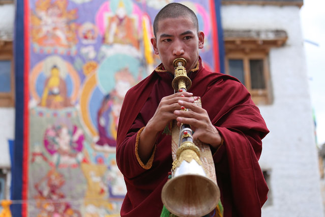 A young monk plays a gyaling, traditional Tibetan horn, during the Tenchi Festival on May 26, 2014 in Lo Manthang, Nepal. The Tenchi Festival takes place annually in Lo Manthang, the capital of Upper Mustang and the former Tibetan Kingdom of Lo. Each spring, monks perform ceremonies, rites, and dances during the Tenchi Festival to dispel evils and demons from the former kingdom. (Photo by Taylor Weidman/Getty Images)