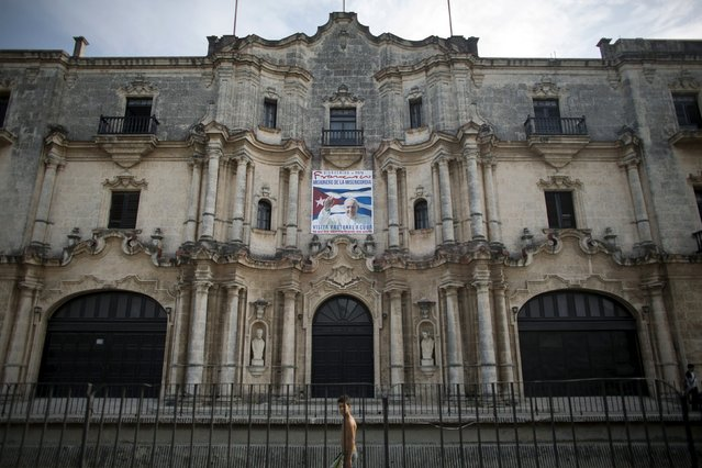 A boy passes by a banner advertising Pope Francis' visit to Cuba, which is expected to take place between September 19 and September 22, in Havana, July 30, 2015. (Photo by Alexandre Meneghini/Reuters)