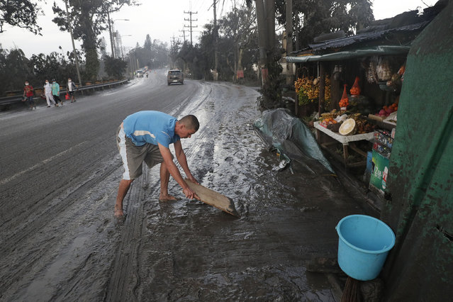 Residents cleans ash fall from Taal Volcano's eruption Monday January 13, 2020, in Tagaytay, Cavite province, south of Manila, Philippines. (Photo by Aaron Favila/AP Photo)