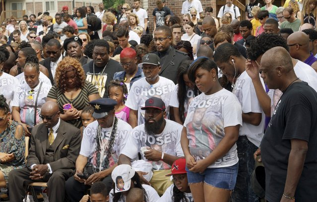 Michael Brown Sr. (C), at the spot where his son was killed, listens with other family members at an event to mark the one-year anniversary of the killing of his son Michael Brown in Ferguson, Missouri August 9, 2015. (Photo by Rick Wilking/Reuters)