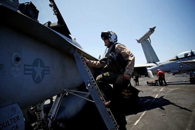 """Navy F/A-18 pilot Commander Higgins from the VFA-83  Squadron also known as the """"Rampagers"""" climbs in to his plane before a mission, on the USS Harry S. Truman aircraft carrier, in the eastern Mediterranean Sea, June 15, 2016. (Photo by Baz Ratner/Reuters)"""