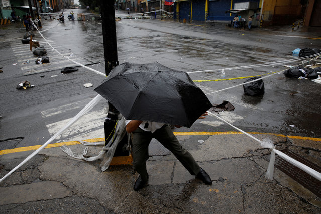 A pedestrian walks through a barricade during a rally against Venezuelan President Nicolas Maduro's government in Caracas, Venezuela on July 19, 2017. (Photo by Carlos Garcia Rawlins/Reuters)