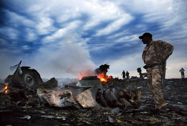 People walk through debris at the crash site of a passenger plane near the village of Grabovo, Ukraine, on Jule 17, 2014.  A Ukrainian official said a passenger plane carrying 295 people was shot down Thursday as it flew over the country, and plumes of black smoke rose up near a rebel-held village in eastern Ukraine. Malaysia Airlines tweeted that it lost contact with one of its flights as it was traveling from Amsterdam to Kuala Lumpur over Ukrainian airspace. (Photo by Dmitry Lovetsky/Associated Press)