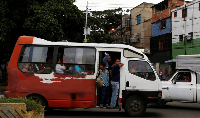People take a ride on a mini bus in Caracas, Venezuela, June 21, 2016. (Photo by Mariana Bazo/Reuters)