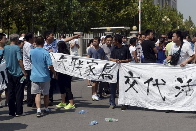 "A policeman gestures as he tries to stop relatives, mostly of missing firefighters, from unfurling a banner during a protest to demand information about those missing following Wednesday's blasts, in front of the Binhai new district government building in Tianjin, China, August 16, 2015. The words on the banner read, ""Give missing people's relatives explanations"". (Photo by Reuters/Stringer)"