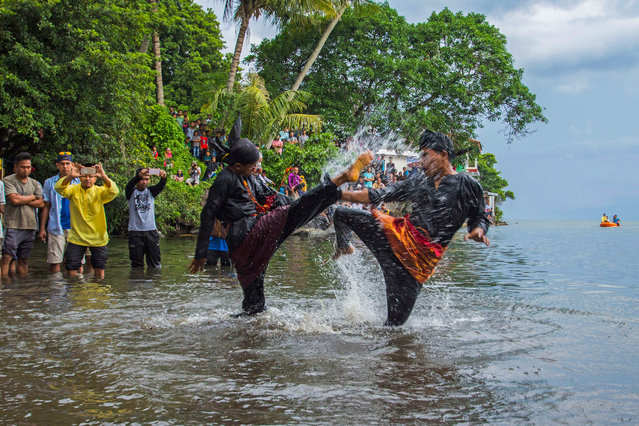 People take part in a traditional martial art form called Silat at Lake Singkarak on July 02, 2017 in West Sumatra, Indonesia. Silek is the Minangkabau name for their indigenous version of martial arts known as silat in other parts of Indonesia and Malaysia. Silek is taught to almost all young boys as an important element of indigenous tradition and custom as a valuable part of their ethnic identity. (Photo by Riau Images/Barcroft Images)