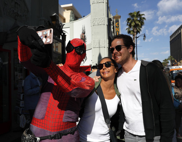 "In this Wednesday, May 24, 2017 photo, superhero impersonator and actor Dan Inigo, left, uses a tourist's smartphone to take a selfie on Hollywood Boulevard in Los Angeles. ""It's a place of diversity, it's a place of drama, it's a place of illusion – a place of broken dreams"", says the 25-year-old actor who prowls the boulevard dressed as Spider-Man. Although he barely scrapes by, Inigo says it's still a great gig for a struggling actor who needs to keep a schedule open for auditions. (Photo by Jae C. Hong/AP Photo)"