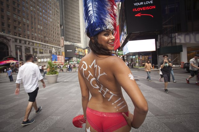A model who poses for tips wearing body paint and underwear poses for a portrait in Times Square in New York, August 19, 2015. She declined to give her name. New York officials including Governor Andrew Cuomo are considering measures to curtail the activity, according to local media. (Photo by Carlo Allegri/Reuters)