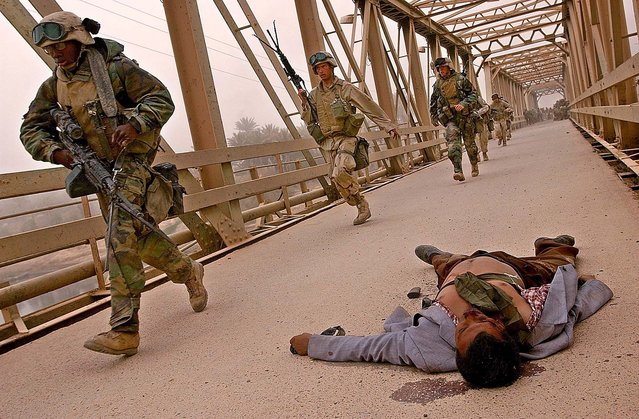 U.S. Marines of 3rd Batallion 4th Marines rush to cross the damaged Baghdad Highway Bridge, Monday, April 7, 2003, passing an Iraqi man's body, as the Marines enter the southeast outskirts of Baghdad