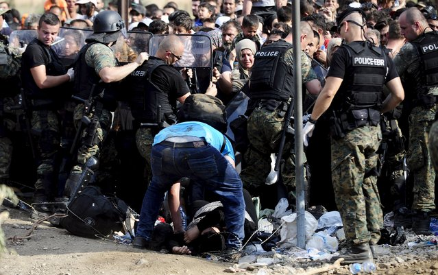 U.N. workers help a woman who collapsed at the border line dividing Macedonia and Greece August 21, 2015. (Photo by Ognen Teofilovski/Reuters)