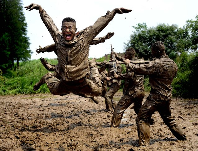 Paramilitary policemen train in the mud in Chuzhou city in central China's Anhui province on July 18, 2012. (Photo by Associated Press)