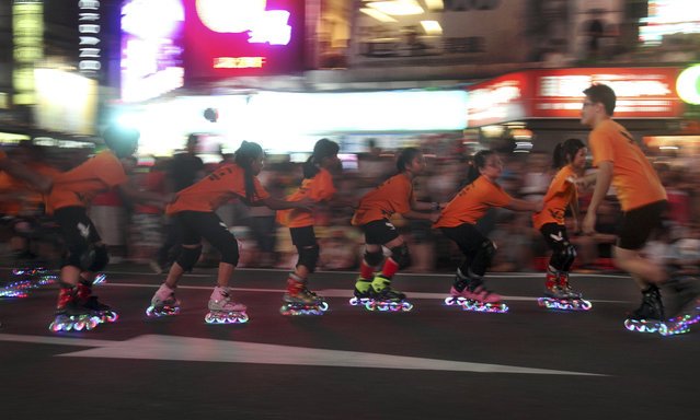 In this photo made late Saturday, August 9, 2014, children perform on inline skates during a parade marking the beginning of the Chinese folklore's mid-summer's Ghost Month Festival. Fourteen days into the seventh month of the lunar calendar, August 9, in 2014, marks the traditional Chinese Ghost Month where the gates of the underworld are opened and spirits of the deceased are set free to roam the world of the living. The month long festivities are aimed to please the roaming spirits. (Photo by Chiang Ying-ying/AP Photo)