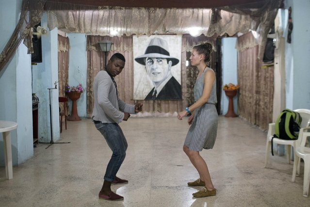 Mechanic and salsa dance instructor Ariel Domninguez, 26, (L), gives a class to Jarman Frash, 25, a medical student from Germany in Havana, February 4, 2015. (Photo by Alexandre Meneghini/Reuters)