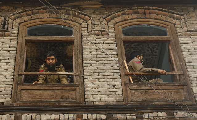 Indian policemen keep guard from the window of a residential house during curfew in Srinagar, Indian controlled Kashmir, Wednesday, July 13, 2016. Curfew imposed in the disputed Himalayan region continues for the fifth consecutive day to suppress anti-India violence following the Friday killing of Burhan Wani, chief of operations of Hizbul Mujahideen, Kashmir's largest rebel group. (Photo by Mukhtar Khan/AP Photo)