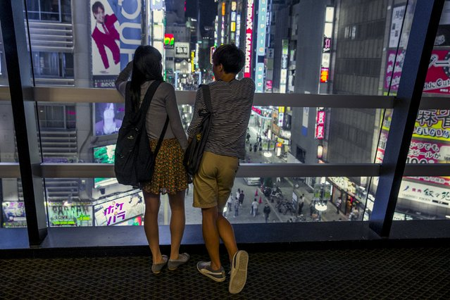 A couple overlooks Shinjuku's nightlife district of Kabukichoi in Tokyo, August 27, 2015. (Photo by Thomas Peter/Reuters)