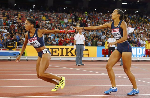 Floria Guei of France (L) receives the baton from Agnes Raharolahy in the women's 4 x 400 metres relay final  during the 15th IAAF World Championships at the National Stadium in Beijing, China, August 30, 2015. (Photo by Kai Pfaffenbach/Reuters)