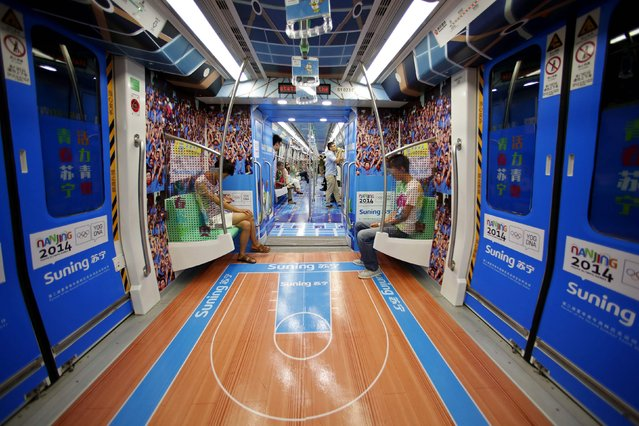 Passengers sit in the carriage of a subway train with floors decorated to resemble a basketball court to celebrate the ongoing 2014 Nanjing Youth Olympic Games in Nanjing, Jiangsu province, August 19, 2014. (Photo by Aly Song/Reuters)