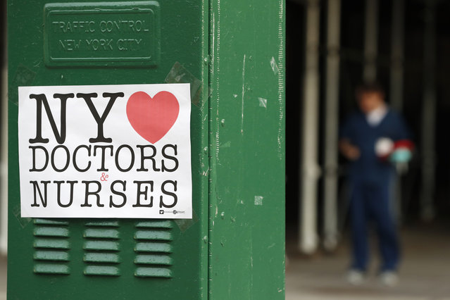 A sign acknowledging the work of doctors and nurses is posted on a traffic control box outside Brooklyn Hospital Center, as a hospital worker, right, waits for a traffic light to change before reporting to duty, Sunday, April 5, 2020, in New York. The Brooklyn hospital is one of several in the area treating high numbers of coronavirus patients. (Photo by Kathy Willens/AP Photo)
