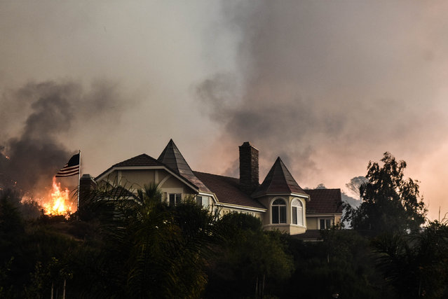A wildfire burns close to a home near Sand Caynon and Placerita Caynon in Santa Clarita, Calif.,  Saturday, July 23, 2016. (Photo by Ryan Babroff/AP Photo)