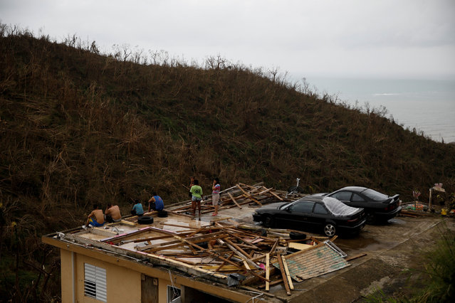 People stay at the roof of a damaged house after the area was hit by Hurricane Maria in Yabucoa, Puerto Rico September 22, 2017. (Photo by Carlos Garcia Rawlins/Reuters)